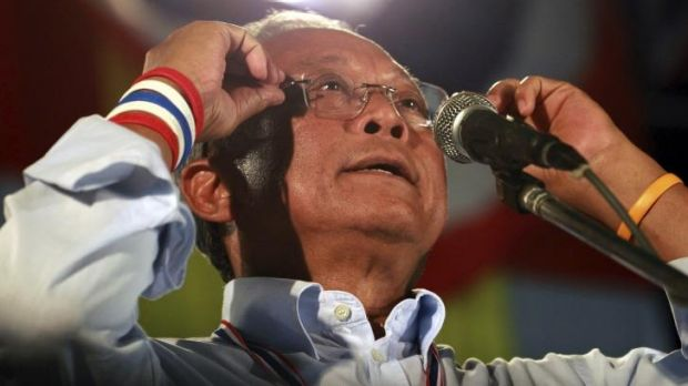 Thai protest leader Suthep Thuagsuban adjusts his glasses while making a speech during an anti-government rally outside ...