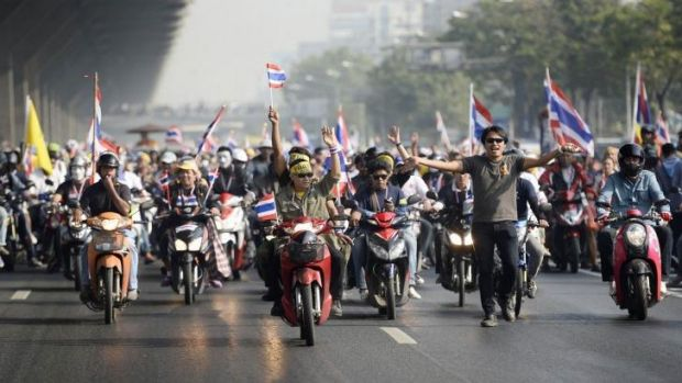 Anti-government protesters with Thai national flags ride their motorbikes as they rally on a main road in Bangkok.