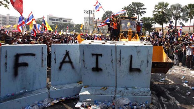 Protesters use a front loader to knock down a concrete barricade outside the Government House in the country's capital.