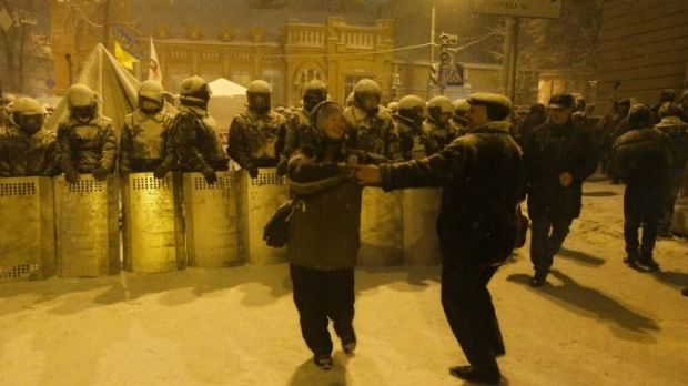A couple dance in front of Ukrainian riot police as they block Pro-European Union activists gathered next to the ...
