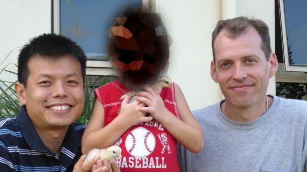 Peter Truong and Mark Newton (at right) with their adopted son known as Boy 1 (his face pixelated).