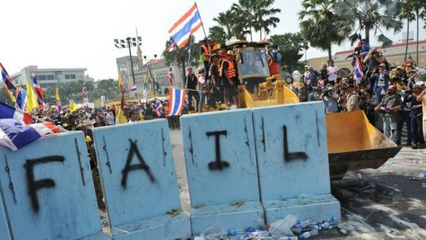 Pressing on: Protesters clear a police barricade near Government House in Bangkok.