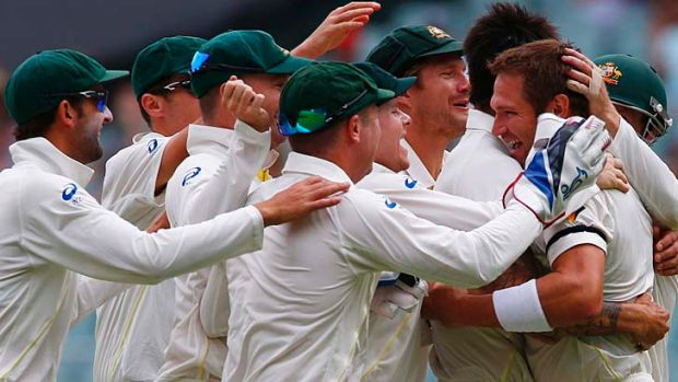 Ryan Harris is mobbed by teammates after taking a catch to dismiss England's captain Alastair Cook on the fourth day of ...
