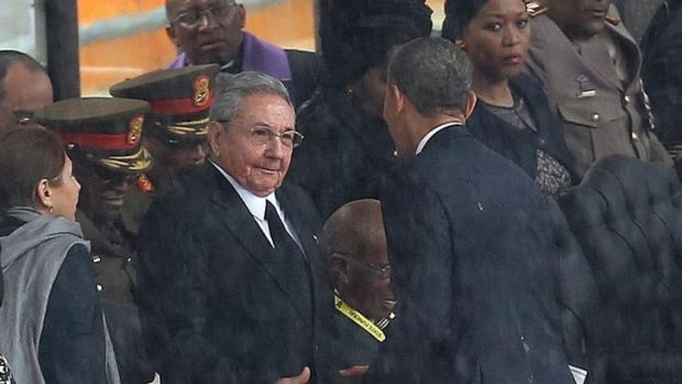 US President Barack Obama shakes hands with Cuban President Raul Castro at the FNB Stadium in Soweto, South Africa, for ...