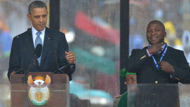 All smiles ... US President Barack Obama delivers a speech next to the fake sign language interpreter during the ...