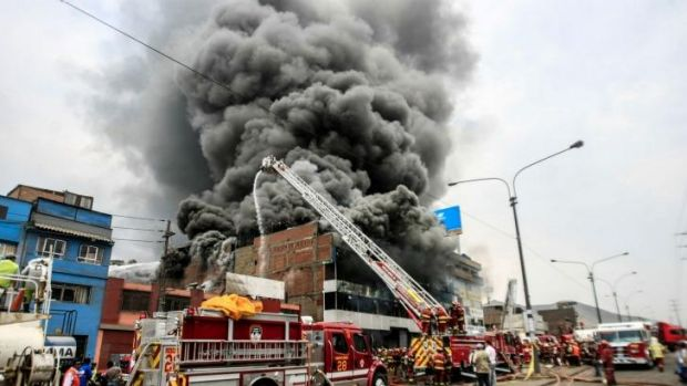 Ablaze: Firefighters attempt to control the fire at a tyre warehouse in downtown Lima.