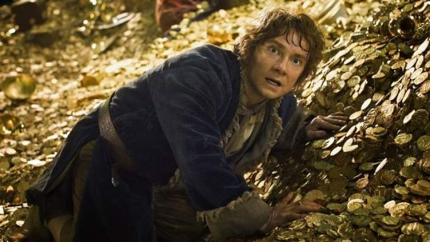 Show me the money: Bilbo rummages among the gold in Smaug's lair.