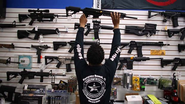 Holding on: Mike Acevedo returns a weapon to its display at the National Armory store in Pompano Beach, Florida.