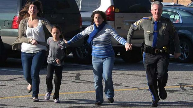 Terror: Two women and a child are led to safety from the Sandy Hook Elementary School massacre.