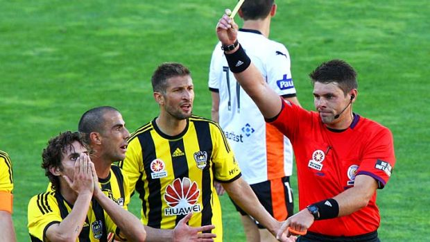 Referee Shaun Evans shows a yellow card to Albert Riera (left) of the Phoenix while teammates Manny Muscat and Vince Lia ...