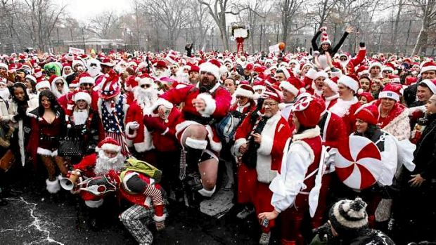 Revelers dressed as Santa Claus pose for a picture at a park during the SantaCon event in New York December 14, 2013. ...