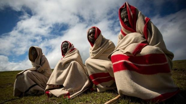 Old ways: Xhosa youths sit on a hillside overlooking Qunu before his funeral cortege arrives.