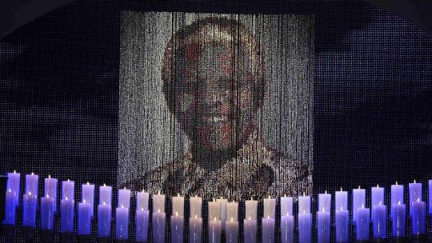 Candles are lit under a portrait of Nelson Mandela before his funeral ceremony.