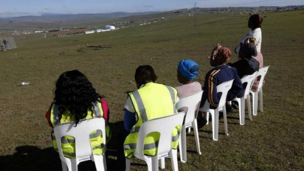 Local women sit on chairs at a public viewing point near the burial ground.