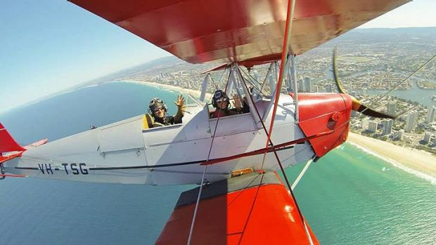 "Pilot Alex James ""Jim"" Rae, 26, and his wife Alice fly a Tiger Moth over the Gold Coast."