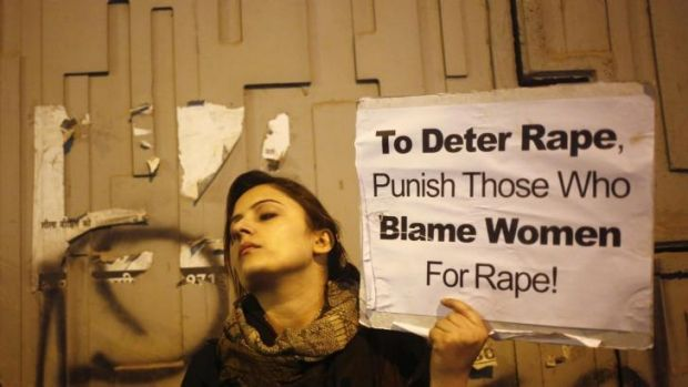 A demonstrator holds a placard as she attends a candlelight vigil to mark the first anniversary of Delhi gang rape, in ...