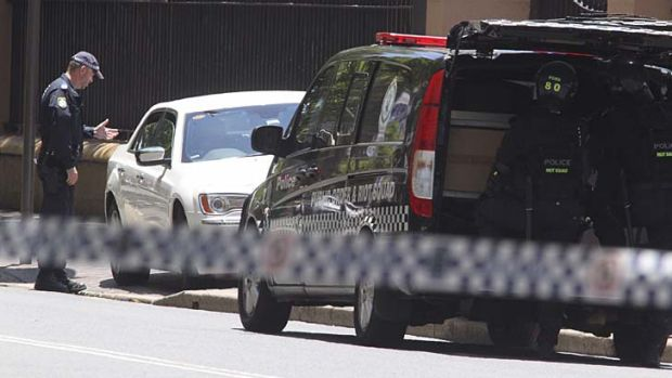 A police officer speaks to the driver of a car that stopped outside NSW Parliament House, sparking a bomb scare.