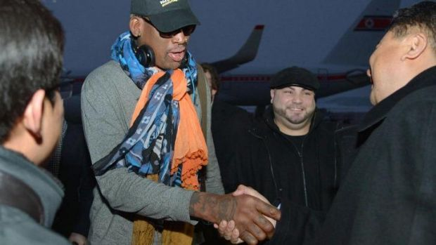 Former basketball star Dennis Rodman greets officials at Pyongyang airport on Thursday.