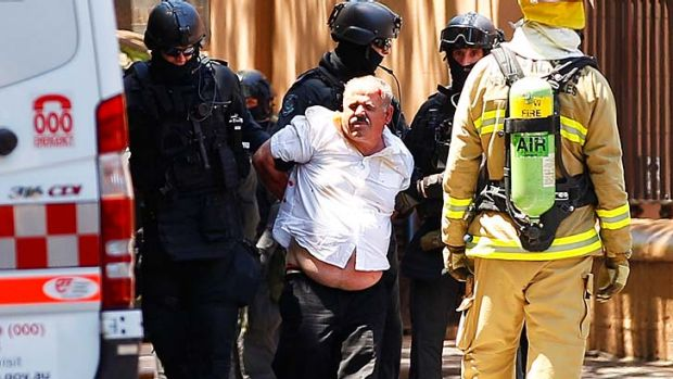 A man whose car was stormed by police outside NSW Parliament House on Friday is taken away.