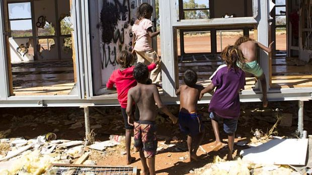 Destroyed: Children play in the wrecked demountable that was supposed to be the new community centre.