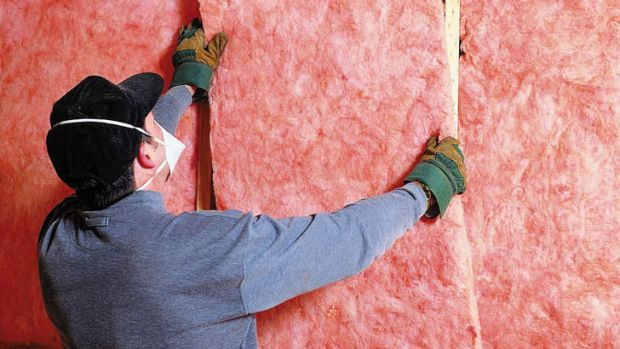 Builder in mask putting in pink batts for insulation.