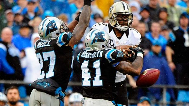 Captain Munnerlyn #41 and Quintin Mikell #27 of the Carolina Panthers break up a pass intended for Marques Colston #12 ...