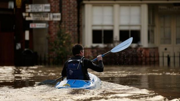 A man canoes along the town centre streets in Yalding, England.