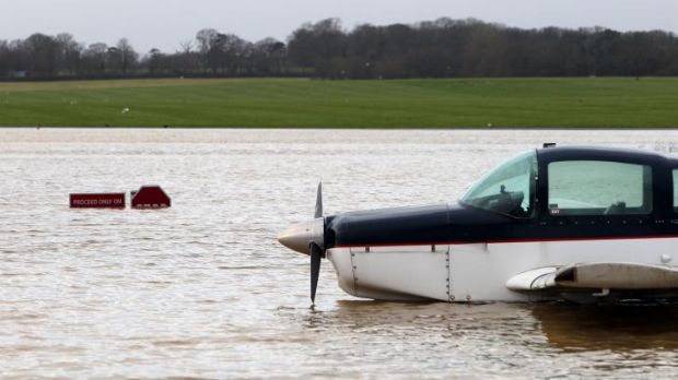 A plane sits in flood water by submerged warning signs following heavy rain, at Redhill Aerodrome in Surrey, England,.