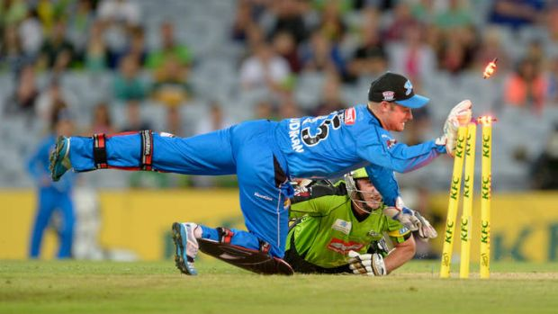 Mike Hussey of the Thunder dives into his crease to avoid being run out by Tim Ludeman of the Strikers.