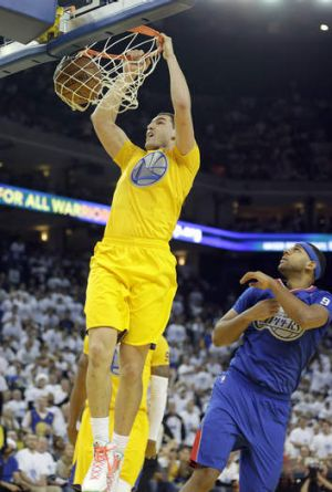 Golden State Warriors guard Klay Thompson slam dunks against Los Angeles Clippers forward Jared Dudley.