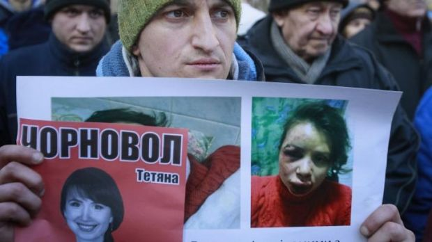 Mounting anger: A protester holds pictures of journalist Tetyana Chornovil, who was beaten and left in a ditch just ...