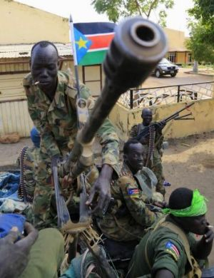 A South Sudan  soldier stands next to a truck-mounted machine gun mounted in Malakal, a few days after government forces ...