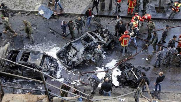 Civilians, soldiers and policemen gather at the site of an explosion in downtown Beirut on December 27. Former Lebanese ...