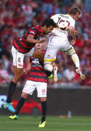 Up for the challenge: Nikolai Topor-Stanley of the Wanderers is beaten to the ball by Wellington's Jeremy Brockie.