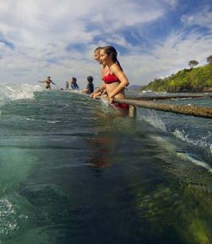 Awash: Simon Abbott and his daughter Amelie enjoy the king tide at Wollongong's Austinmer Beach.