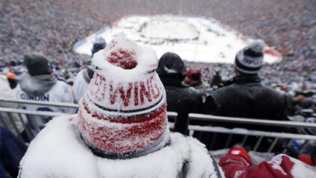 A Detroit Red Wings fan, coated with snow, watches the Winter Classic outdoor NHL hockey game against the Toronto Maple ...