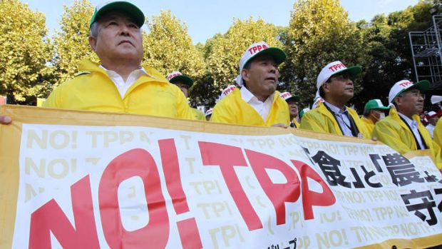 Farmers hold a banner as they take part in a rally against Japan's participation for negotiations in the U.S.-led ...