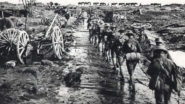 Australian troops in Flanders trudge along a timber road sinking into the mire.