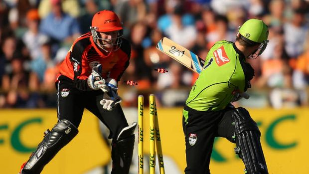 Ryan Carters of the Thunder is bowled by Brad Hogg of the Scorchers.
