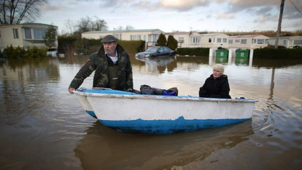 Ian Peacock pulls a boat carrying fellow resident Caroline Hine as they rescue possesions from flooded caravans at the ...