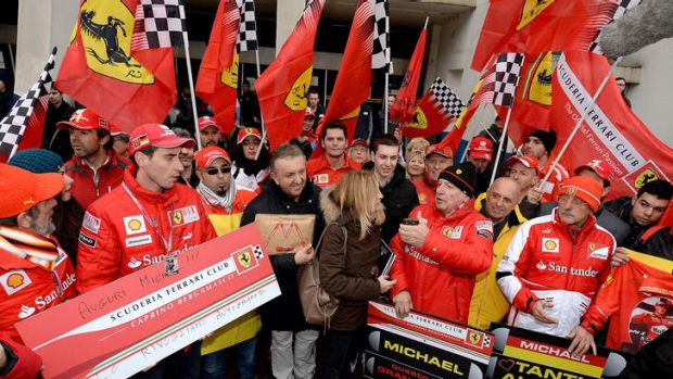 Fans of Michael Schumacher gather in front of the main entrance of Grenoble University Hospital Centre.