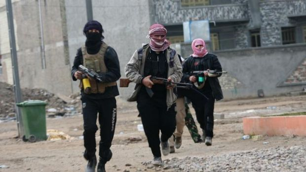 Unidentified gunmen patrol during clashes with Iraqi forces in Fallujah on Sunday.
