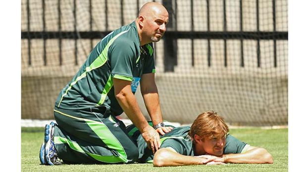 Australian physiotherapist Alex Kountouris works on Shane Watson's back before the Boxing Day Test.
