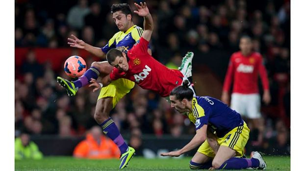 Manchester United's Javier Hernandez (centre) is brought down by Swansea City's Chico (bottom right) as Neil Taylor ...
