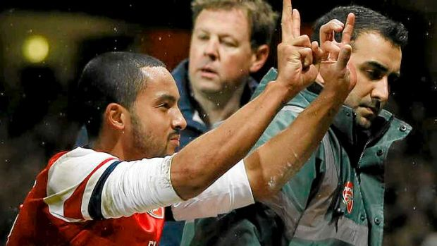What's the score: Theo Walcott gestures to the Spurs fans the score of 2-0.