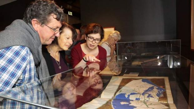 The McLays are shown a world map in Geographia, by Claudius Ptolemy, by Mapping Our World co-curator Susannah Helman.