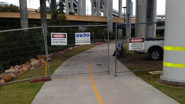 Signs on fences blocking the path have warned of asbestos being removed.