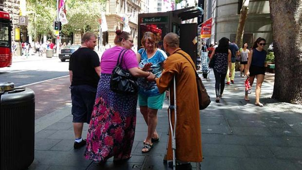 A man dressed as a monk and using crutches approaches people at Martin Place.