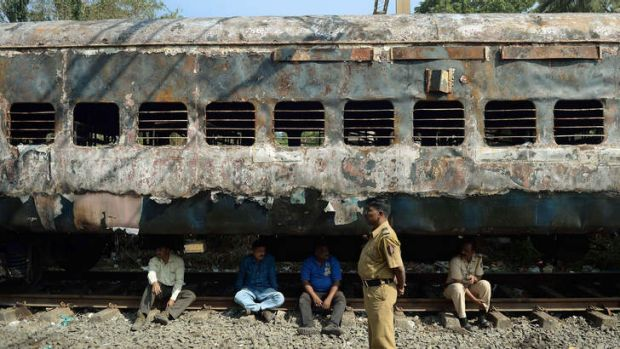 After the fire: Indian railway officials sit beneath a burnt-out carriage.