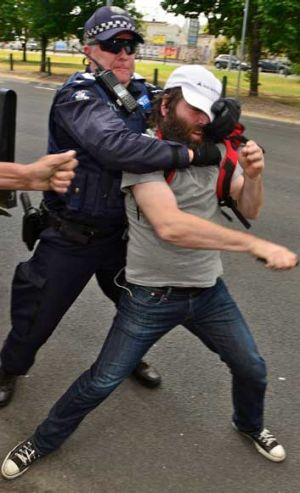 Police grab a protester.